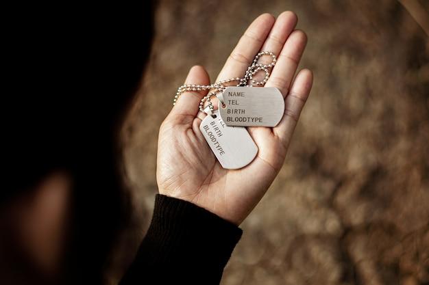 Tag de cão militares em branco na mão das mulheres. - conceito de memórias e sacrifícios.