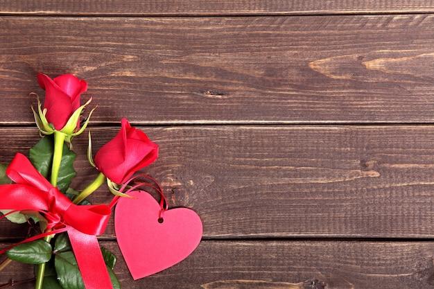 Tag do presente do valentim e rosas vermelhas na placa de madeira