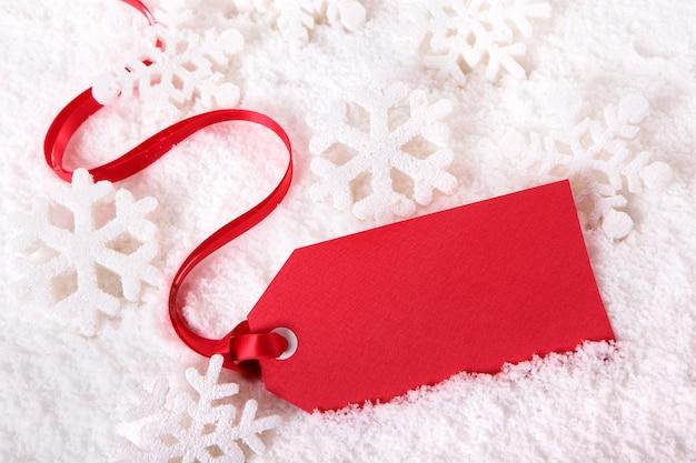 Tag do presente ou bilhete vermelho do preço com fita vermelha em um fundo da neve.