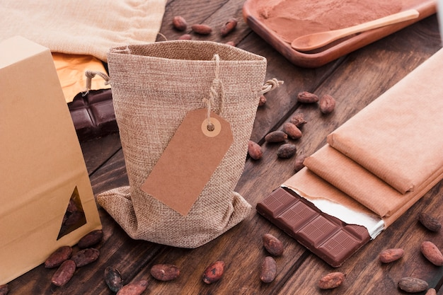 Tag em branco no saco com grãos de cacau espalhados e barra de chocolate na mesa