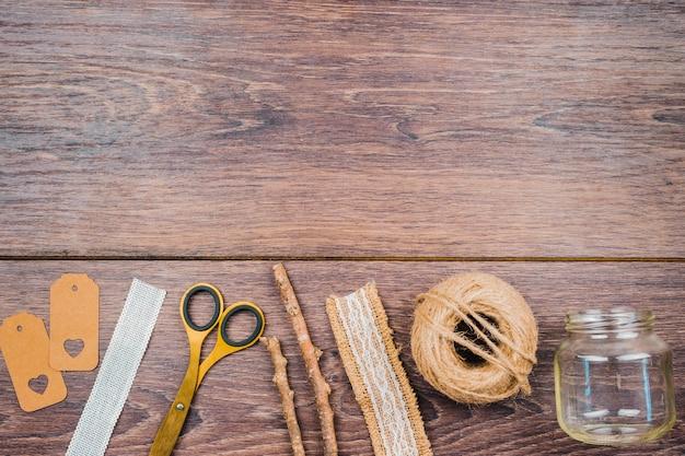 Tag; fita; tesoura; varas; carretel de juta e um frasco transparente vazio na mesa de madeira