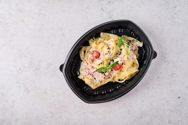 Tagliatelle carbonara em recipiente de plástico preto com luz de fundo vista de cima conceito de designer de comida