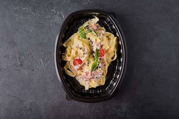 Tagliatelle carbonara em recipiente de plástico preto sobre fundo de grafite escuro vista de cima comida de grife
