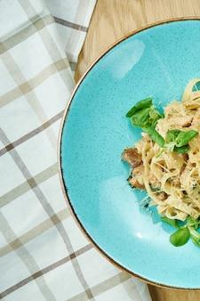 Tagliatelle com frango, molho branco e parmesão em uma tigela azul na mesa de madeira. massa italiana caseira tradicional. fechar-se