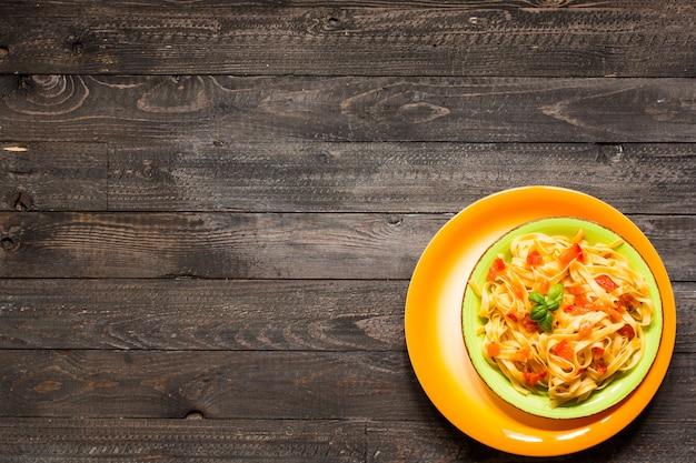 Tagliatelle com tomate e manjericão feitos em casa em um fundo de madeira.
