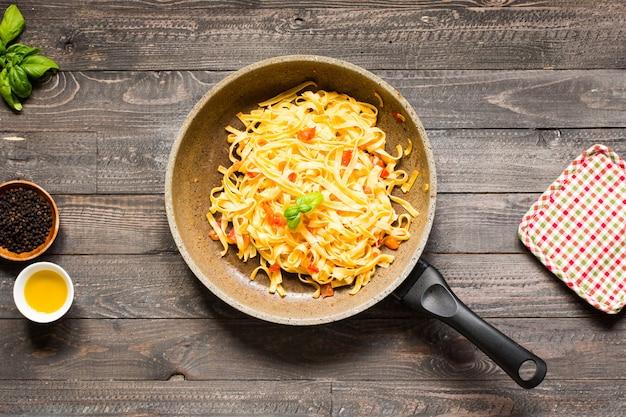 Tagliatelle com tomate e manjericão, feitos em casa, em uma mesa de madeira,