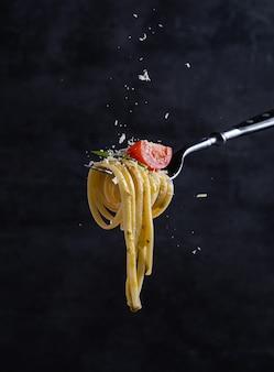 Tagliatelle com tomate e pesto no garfo. comida italiana. fundo escuro