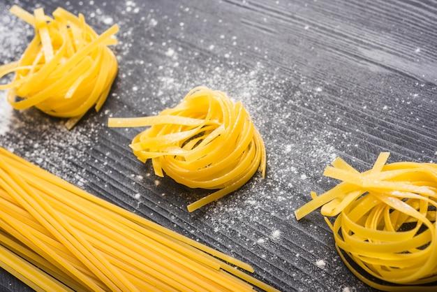 Tagliatelle cru e espaguete em pano de fundo preto de madeira