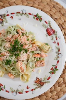 Tagliatelle de frutos do mar com filé de salmão com queijo de ervas servido em prato com decoração natalina