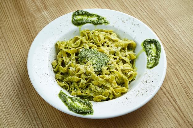 Tagliatelle de massa italiana tradicional com molho pesto e parmesão em um prato branco sobre uma superfície de madeira