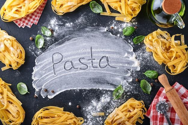 Tagliatelle. massa caseira, folhas de manjericão, farinha, pimenta, azeite e tomate cereja em fundo preto escuro. conceito de comida. brincar. horizontal com espaço de cópia.