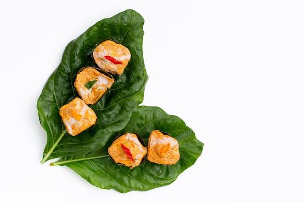 Tailandês com caril de peixe em folhas de bananeira em folhas de noni ou morinda citrifolia na superfície branca.