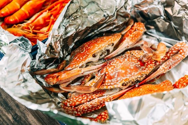 Tailandês cozido no vapor caranguejos da flor no shell que envolvem com papel alumínio.