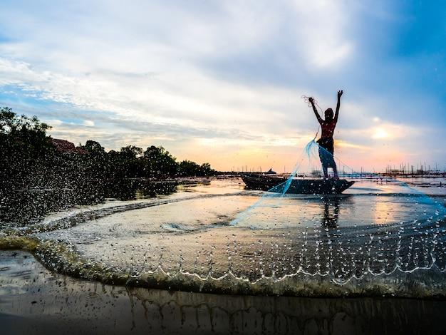 Tailândia pescador jogando a rede de pesca captura peixe causando respingos de água