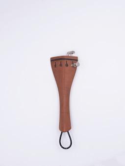 Tailpiece de violino colocado no fundo branco. parte do instrumento acústico