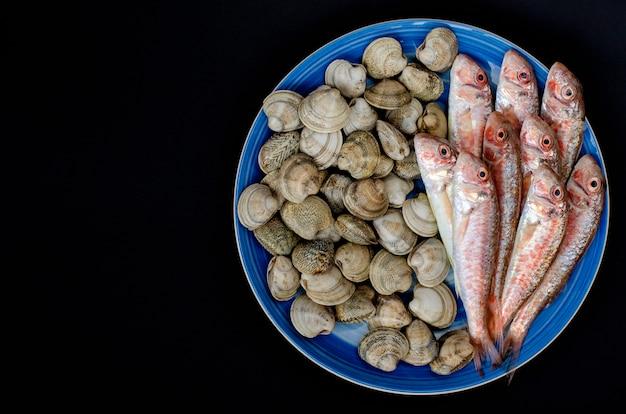 Tainha vermelha fresca e moluscos ou marisco na placa azul. conceito de frutos do mar mediterrâneo