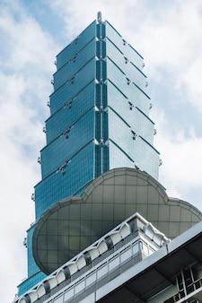 Taipei 101 construções de baixo com o céu azul e a nuvem brilhantes em taipei, taiwan.