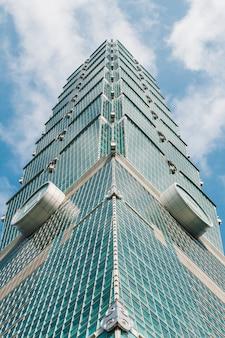 Taipei 101 que constrói essa vista de baixo com do céu azul e da nuvem brilhantes.