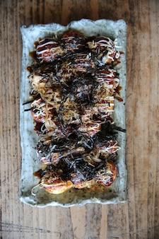 Takoyaki em fundo de madeira, comida japonesa