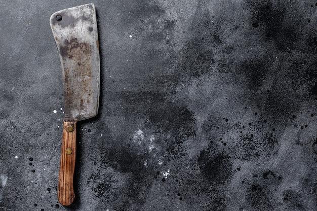 Talhador de carne na textura preta riscada velha. fundo escuro. vista do topo. copie o espaço