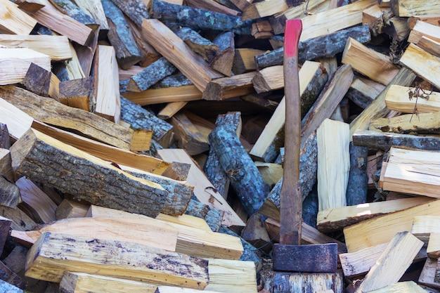 Talhador de machado e um monte de faia picada, hornbeam e lenha de cinzas
