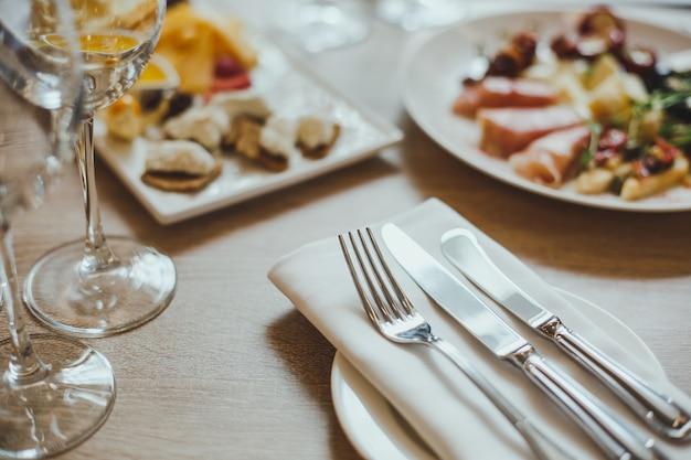 Talheres, aperitivos e taças de vinho na mesa de madeira no restaurante.