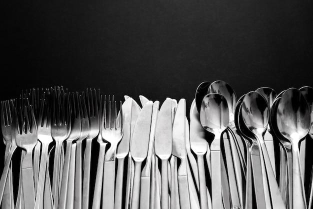 Talheres básicos e simples de aço inoxidável, constituídos por facas, colheres e garfos, isolados em fundo preto com espaço de cópia.