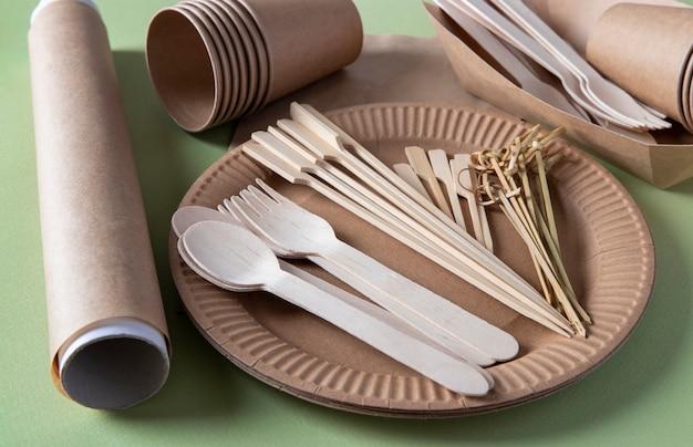 Talheres biodegradáveis descartáveis em pratos de papel artesanal - garfos, colheres, copos, espetos de bambu e pergaminho