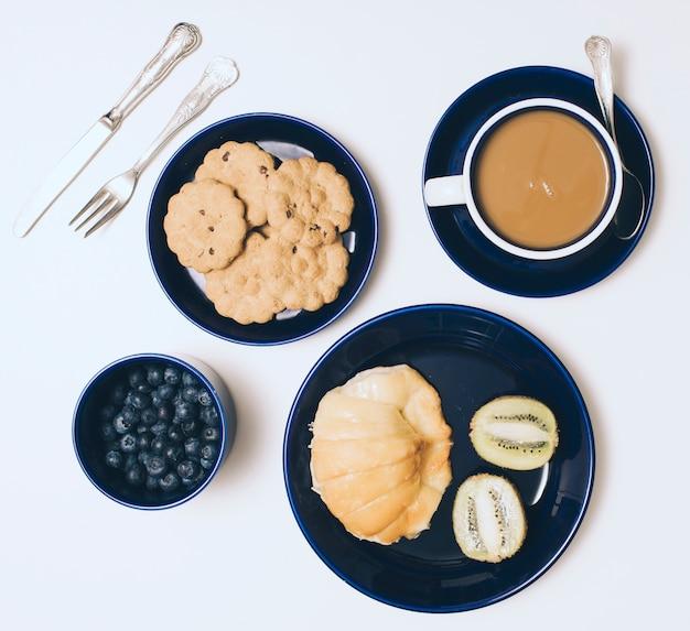 Talheres; biscoitos; kiwi; amoras; xícara de café e pão no fundo branco