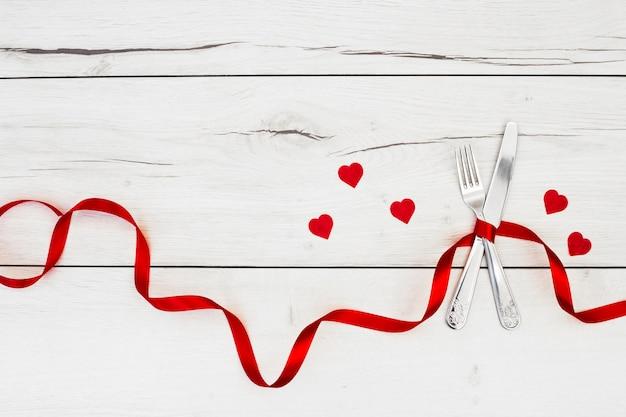 Talheres com fita perto de corações de ornamento