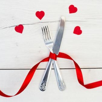 Talheres com fita vermelha perto de corações de ornamento