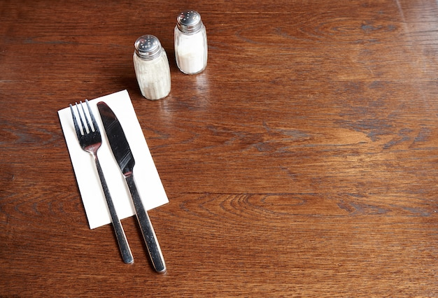 Talheres com sal e pimenta em uma mesa rústica