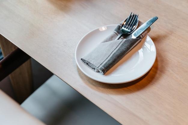 Talheres conjunto incluindo colher, garfo, faca e guardanapo na chapa branca na mesa de madeira.