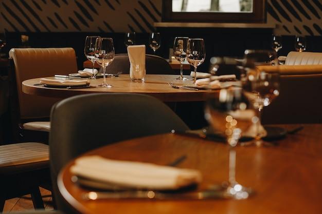 Talheres, copos, garfo de flores e faca servidos no jantar em restaurante com interior aconchegante