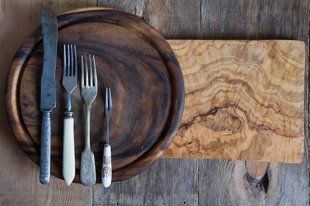 Talheres de aço inoxidável em uma tábua de madeira