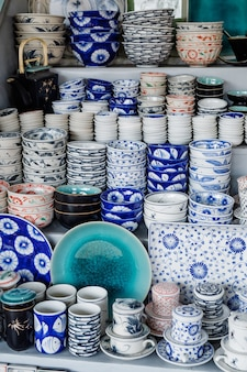 Talheres de cerâmica coloridos, canecas, tigelas e tigelas de comida podem ser encontrados no mercado de souvenirs turísticos em hoi an, vietnã.