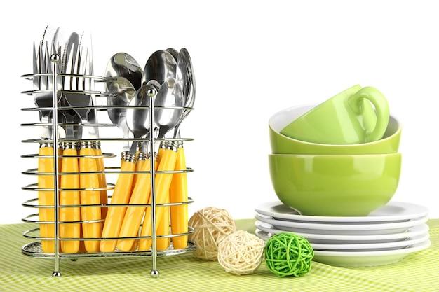 Talheres de cozinha em suporte de metal com toalha de mesa limpa em superfície branca