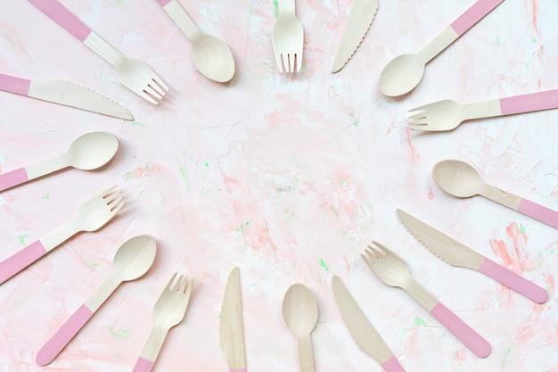 Talheres de madeira amigável eco descartável em fundo rosa, muitas colheres, facas e talheres garfos. zero conceito de resíduos, reciclagem. alternativa sem plástico para proteção ambiental. copie o espaço