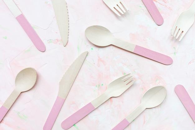 Talheres de madeira amigável eco descartável em fundo rosa, muitas colheres, facas e talheres garfos. zero conceito de resíduos, reciclagem. alternativa sem plástico para proteção ambiental