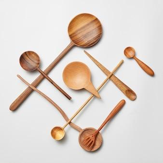 Talheres de madeira variados - colher de pau e faca isoladas no fundo branco