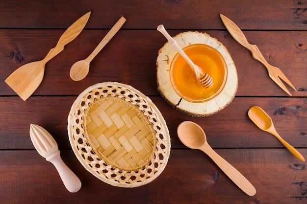 Talheres de madeira, vista superior. talheres e mel em tábuas de madeira.