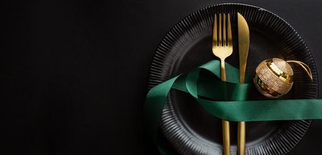Talheres de natal dourado no prato com bugiganga e fita em fundo escuro. bandeira