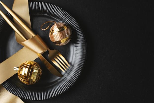 Talheres de natal dourado no prato com bugiganga e fita em fundo escuro.