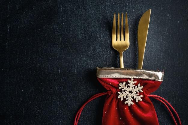 Talheres de natal dourados em uma pequena bolsa têxtil com floco de neve e fita em fundo escuro.
