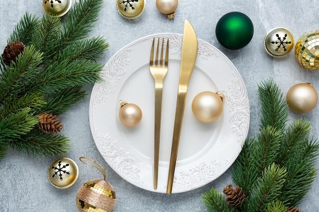 Talheres de natal no prato com decoração de natal na mesa.