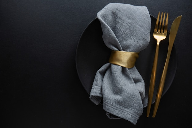 Talheres de ouro com têxteis no prato em fundo escuro. vista do topo.