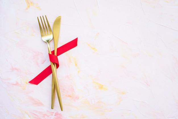Talheres de ouro em fita vermelha em um fundo rosa