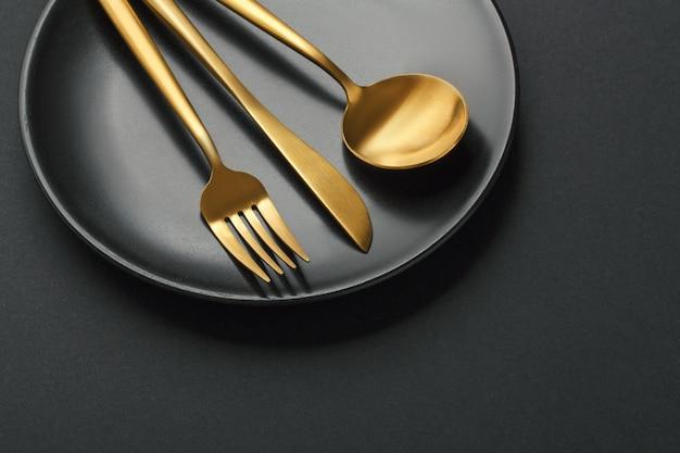 Talheres de ouro em fundo preto