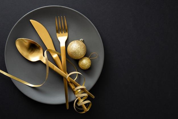 Talheres de ouro servido no prato para o jantar de natal