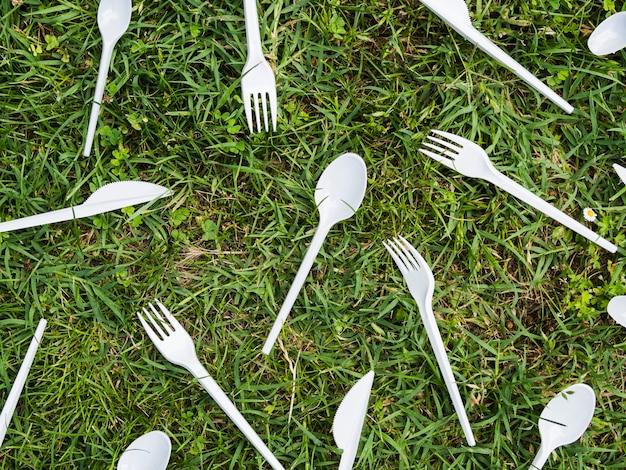 Talheres de plástico branco na grama verde no parque